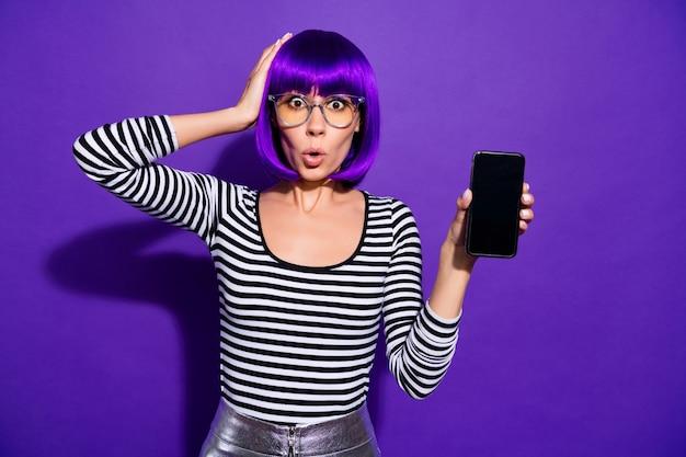Portret van verbaasd duizendjarige aanrakingshoofd met hand die moderne technologie houdt die over violette purpere achtergrond wordt geïsoleerd