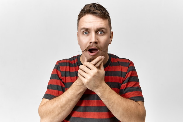 Portret van verbaasd emotionele hipster man met snor zijn baard aanraken en mond openen in shock, met verbaasde vergeetachtige blik. geschokt gefrustreerde jongeman vergat thuis zijn portemonnee
