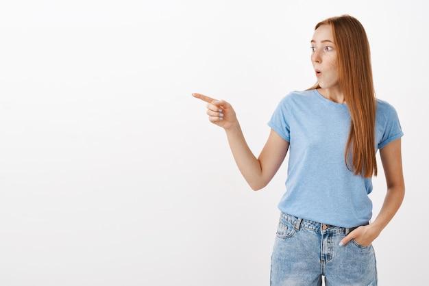 Portret van verbaasd en onder de indruk sprakeloze schattige roodharige vrouw in blauw t-shirt met vouwende lippen fluitend van interesse en verrassing kijkend en wijzend naar links verbaasd