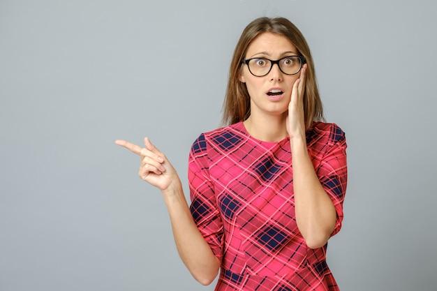 Portret van verbaasd en opgewonden brunette vrouw wijst met wijsvinger