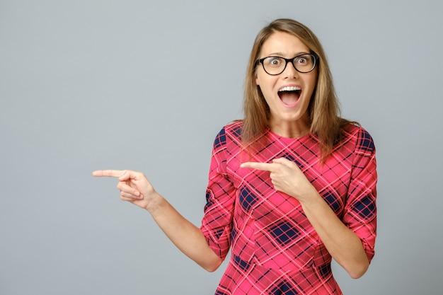 Portret van verbaasd en opgewonden brunette vrouw wijzend met wijsvinger