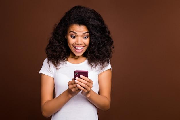 Portret van verbaasd gekke afro-amerikaanse meid blogger gebruik mobiele telefoon krijg sociale netwerkmelding kijk schreeuw wow omg draag wit t-shirt.