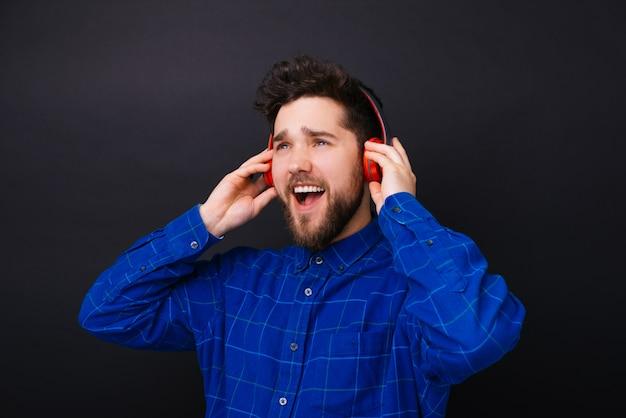 Portret van verbaasd jonge man luisteren muziek op koptelefoon
