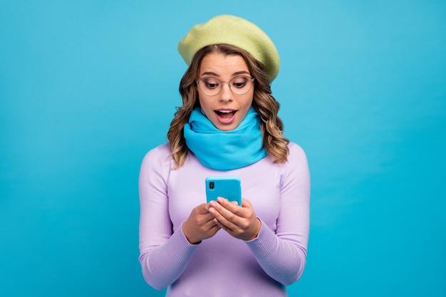 Portret van verbaasd meisje gebruik mobiele telefoon opgewonden gezicht op turkooizen muur