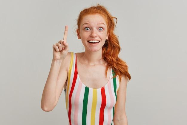 Portret van verbaasd meisje met gember paardenstaart en sproeten, gestreepte kleurrijke zwembroek dragen