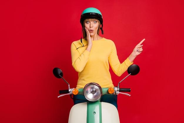 Portret van verbaasd meisje motorrijder rijden motorfiets onder de indruk directe vinger lege ruimte