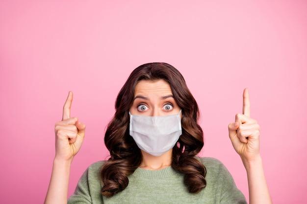 Portret van verbaasd meisje wijsvinger copyspace wijzen op covid infectie quarantaine nieuws draag medisch masker trui pullover jumper geïsoleerd over pastel kleur achtergrond