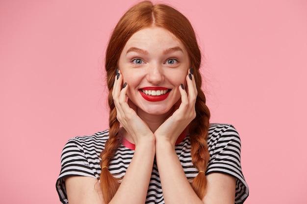 Portret van verbaasd mooi roodharig meisje met twee vlechten houdt handen in de buurt van haar gezicht en lacht levendig met rode lippen, kijkend met wijd geopende gelukkige blauwe ogen, geïsoleerd