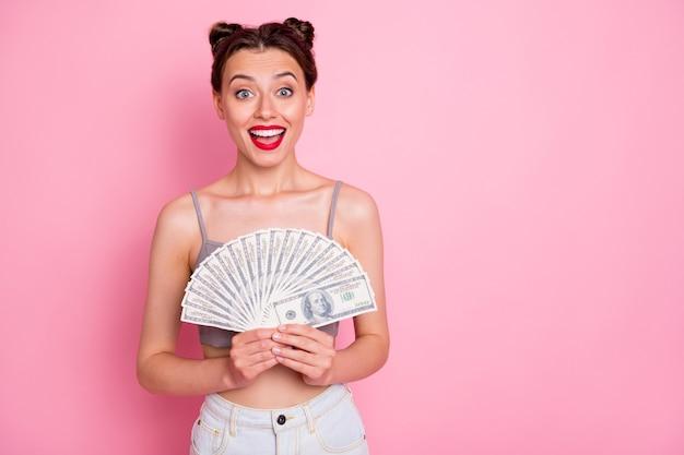 Portret van verbaasd verbaasd meisje houd geld ventilator ze wint loterij krijg miljoen dollar bank voel onder de indruk schreeuw wow omg draag moderne dure kleding geïsoleerde roze kleur