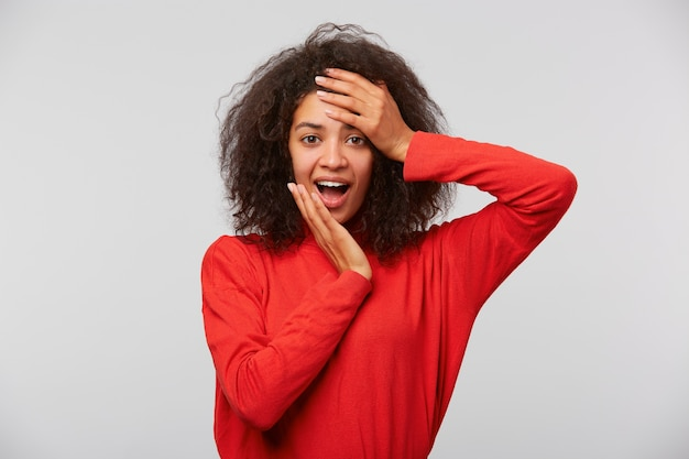 Portret van verbaasd verbaasd mooie vrouw met afro kapsel open mond naar voren kijken, glimlachend