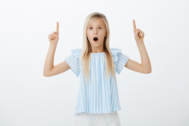 Portret van verbaasd verbaasd schattig jong meisje met blond haar, kaak laten vallen van verwondering en naar boven gericht, prachtig nieuws delen met zus, opgewonden en opgewonden over grijze muur