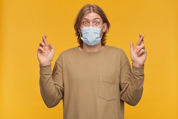 Portret van verbaasd, volwassen mannetje met blond haar en baard. beige trui en medisch beschermend gezichtsmasker dragen. houdt de vingers gekruist. geïsoleerd over gele muur