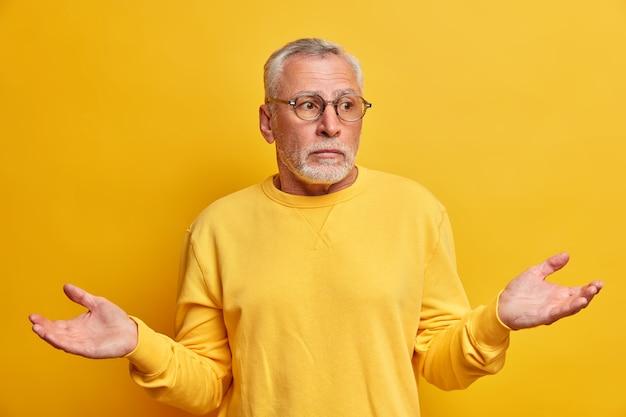 Portret van verbaasde aarzelende bebaarde volwassen man spreidt handpalmen en gezichten moeilijke keuze ziet er onzeker uit draagt casual trui optische bril heeft verwarde uitdrukking geïsoleerd over gele muur