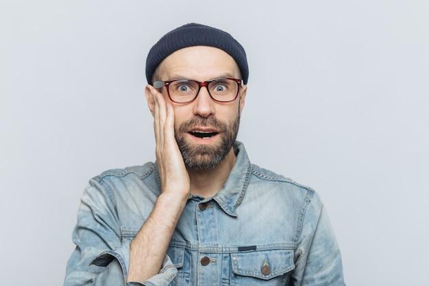 Portret van verbaasde bebaarde opgewonden man kijkt met verrassing