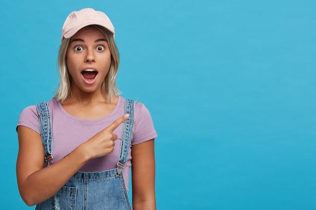 Portret van verbaasde blonde jonge vrouw met geopende mond draagt roze pet, violet t-shirt en denim overall voelt geschokt en wijst naar de zijkant geïsoleerd over blauwe muur