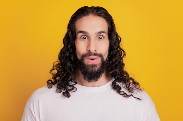 Portret van verbaasde funky man open mond omg reactie op gele achtergrond