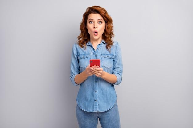 Portret van verbaasde gekke vrouw gebruik mobiele telefoon lees sociale media ongelooflijke nieuwigheid onder de indruk schreeuw wow omg draag moderne kleding geïsoleerd over grijze kleur muur