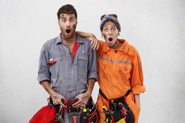 Portret van verbaasde geschokte elektriciens beseft dat ze tijdens het werk een fout hebben gemaakt