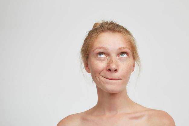 Portret van verbaasde jonge aantrekkelijke roodharige vrouw met natuurlijke make-up haar lippen bijten terwijl peinzend naar boven kijken, geïsoleerd op witte achtergrond