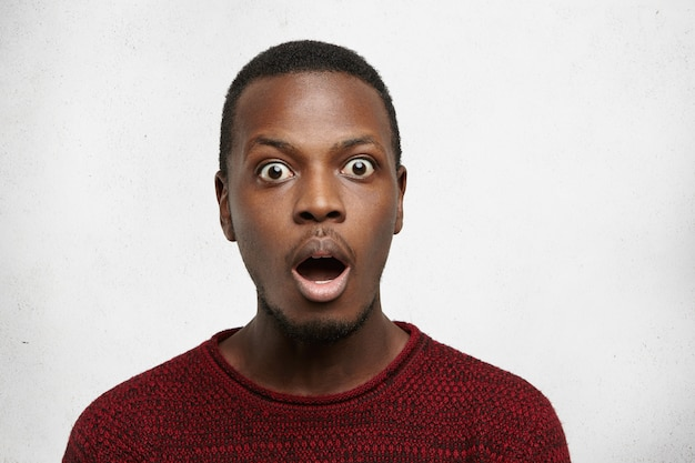 Portret van verbaasde jonge afrikaanse amerikaanse man met grote ogen, terloops gekleed kijkend met opengevallen mond en met open mond, schokkend nieuws niet te geloven