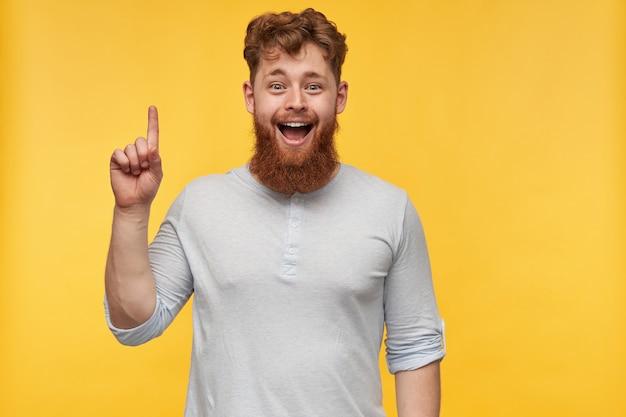 Portret van verbaasde jonge bebaarde man met rood haar, glimlacht breed met gelukkige gezichtsuitdrukking, wijs met een vinger naar boven.