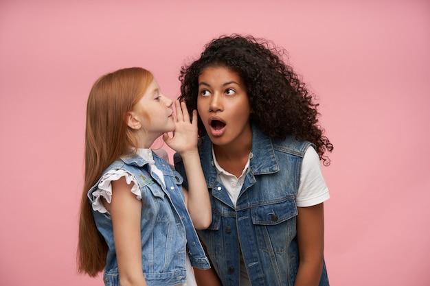 Portret van verbaasde jonge donkerhuidige brunette vrouw met lang krullend haar luisteren naar opgewonden nieuws en haar mond wijd open houden, poseren tegen roze