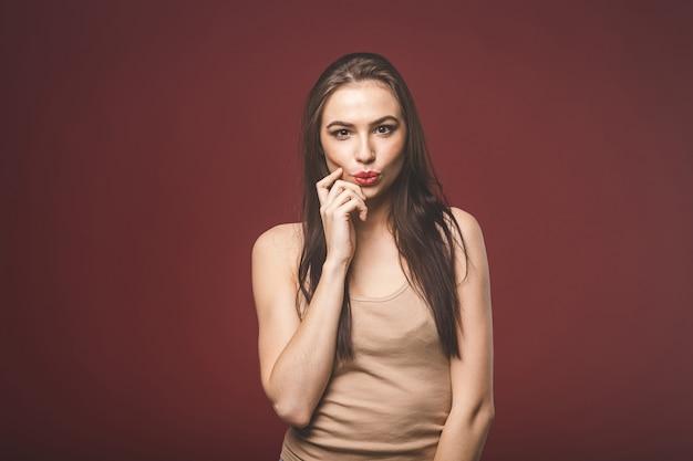 Portret van verbaasde jonge vrouw geïsoleerd op rode achtergrond.