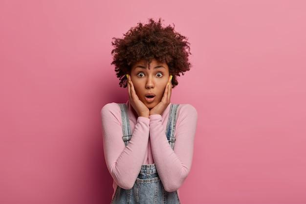 Portret van verbaasde krullende vrouw grijpt gezicht en staart met afgeluisterde ogen, roddelen over iets geweldigs, nonchalant gekleed, poseert tegen roze muur, angstig voor een vreselijk ongeluk.