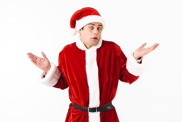 Portret van verbaasde man 30s in kerstman kostuum en rode hoed handen overgeven