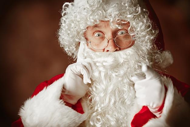 Portret van verbaasde man in kerstman kostuum met een luxe witte baard, kerstmuts en een rood kostuum op rood