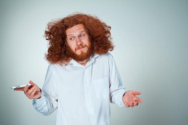 Portret van verbaasde man met lang rood haar, praten aan de telefoon op een grijs