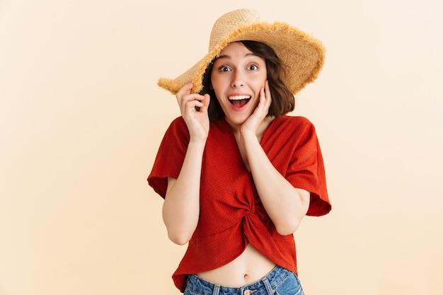 Portret van verbaasde onder de indruk vakantievrouw die strohoed draagt die geïsoleerde verrassing uitdrukt