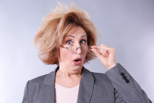 Portret van verbaasde senior vrouw met bril