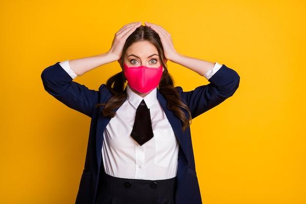 Portret van verbaasde studente hoort vreselijke covid-19-informatie raak hoofd medisch masker aan