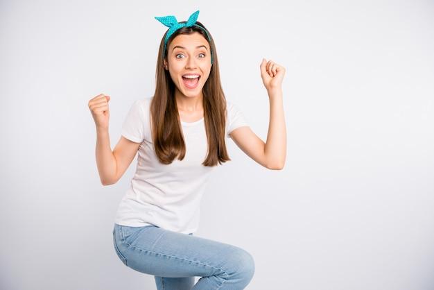 Portret van verbaasde uitdrukking meisje hoort geweldig nieuws en schreeuwen, vuisten heffen viert overwinning