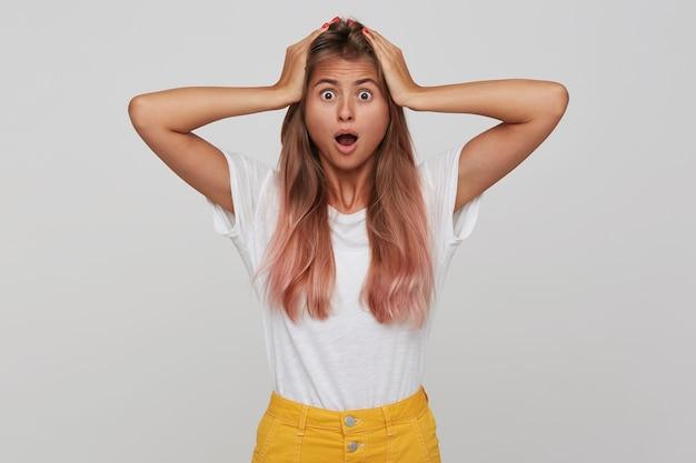 Portret van verbaasde verbaasde jonge vrouw met lang geverfd pastelroze haar en geopende mond houdt handen op het hoofd en schreeuwen geïsoleerd over witte muur