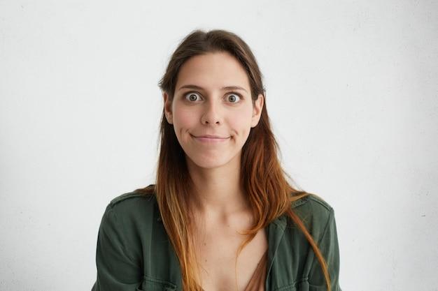 Portret van verbaasde verraste vrouw met sluik lang haar en grote donkere ogen met samengeperste lippen die zich verward voelen met wat problemen.