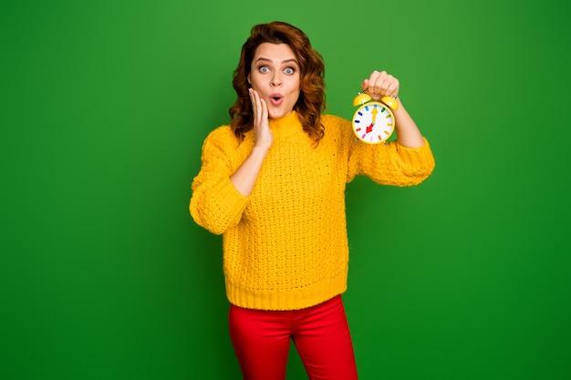 Portret van verbaasde vrouw opstaan houden klok kijken tijd onder de indruk aanraking hand gezicht schreeuwen omg wow slijtage stijl trendy trui geïsoleerd over heldere glans kleur muur