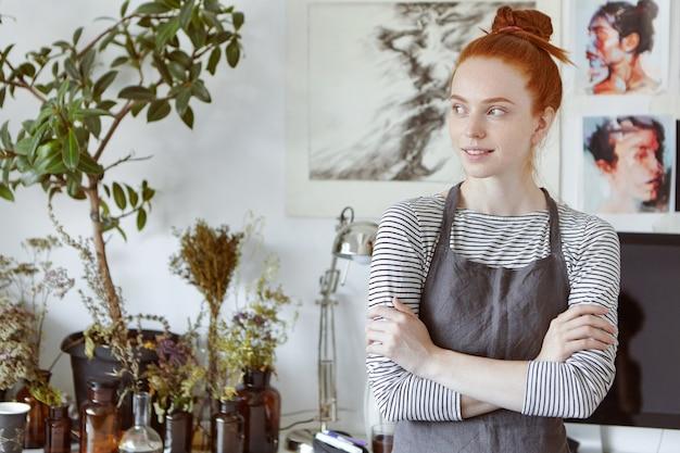 Portret van verbazingwekkende jonge naaister met gember haar en sproeten dragen schort staande in de moderne werkplaats ruimte interieur, wegkijken met dromerige doordachte glimlach, haar armen gevouwen