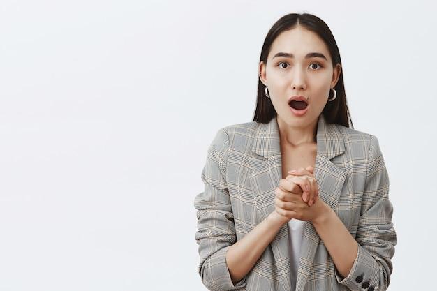 Portret van verbijsterde en geschokte knappe aziatische vrouw, handen over de borst geklemd en hijgend van opwinding en verbazing