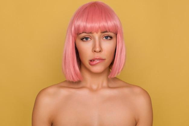 Portret van verbijsterde jonge aantrekkelijke vrouw met kort roze bobkapsel die zorgelijk naar de camera kijkt en onderlip bijt terwijl ze tegen mosterdmuur staat
