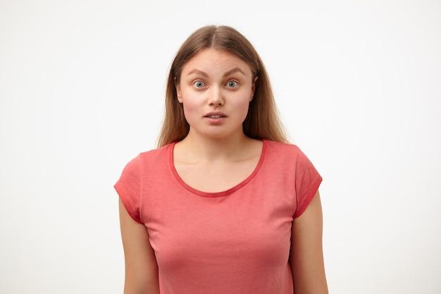 Portret van verbijsterde jonge blonde vrouw verbaasd ogen afronden terwijl ze verbaasd naar de camera kijkt, handen naar beneden houden terwijl poseren op witte achtergrond