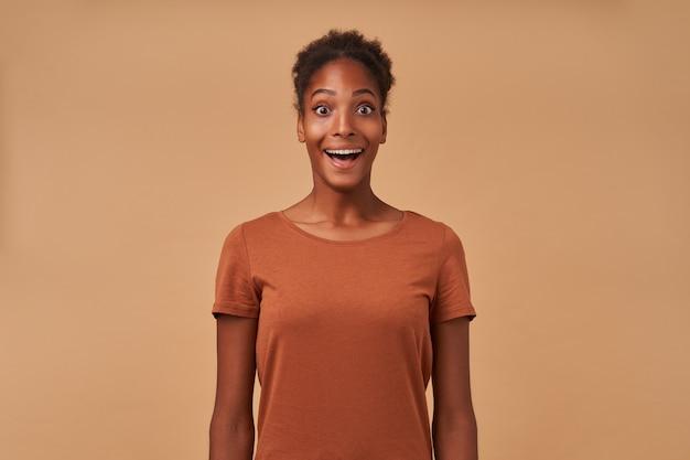 Portret van verbijsterde jonge krullende brunette vrouw houdt haar mond wijd open terwijl ze verrast kijkt, geïsoleerd op beige in vrijetijdskleding
