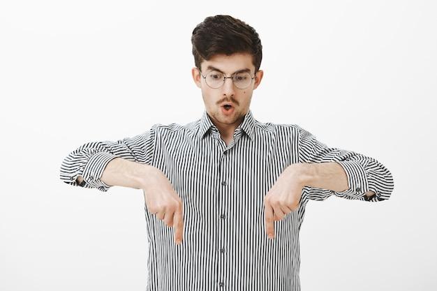 Portret van verbijsterde sprakeloze jongeman in stijlvolle bril en gestreept overhemd, kijkend en wijzend naar beneden terwijl hij zijn kaak laat vallen, iets ongelooflijks ziet, zich verbaasd voelt terwijl hij over een grijze muur staat