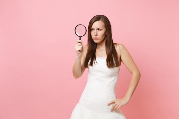 Portret van verdachte vrouw in witte jurk die door vergrootglas kijkt