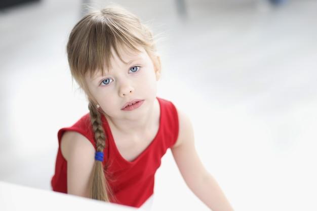 Portret van verdrietig meisje in rode jurk psychologische problemen bij kinderen concept