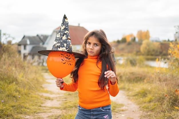 Portret van verdrietig meisje met bruin haar rennen en springen. grappige kinderen in carnavalskostuums buitenshuis.
