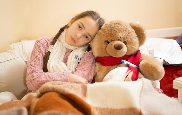 Portret van verdrietig meisje met griep liggend in bed met teddybeer