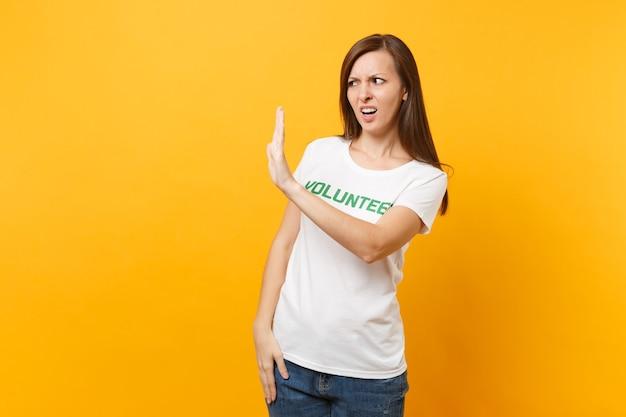 Portret van verdrietig overstuur geschokt jonge vrouw in wit t-shirt met schriftelijke inscriptie groene titel vrijwilliger geïsoleerd op gele achtergrond. vrijwillige gratis hulp, liefdadigheidswerkconcept.