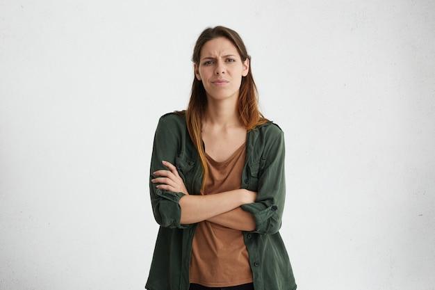 Portret van verergerde droevige vrouw met lang gezicht en gezonde huid die zich gekruiste handen bevinden die haar ontevredenheid uitdrukken